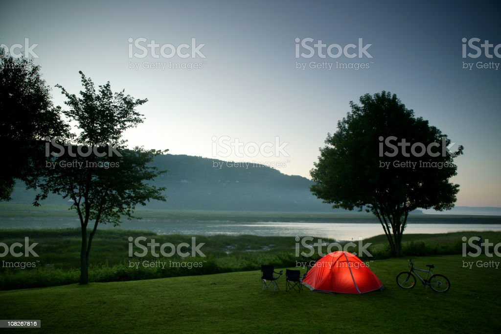 camping tent nearby river and mountain at night royalty-free stock photo