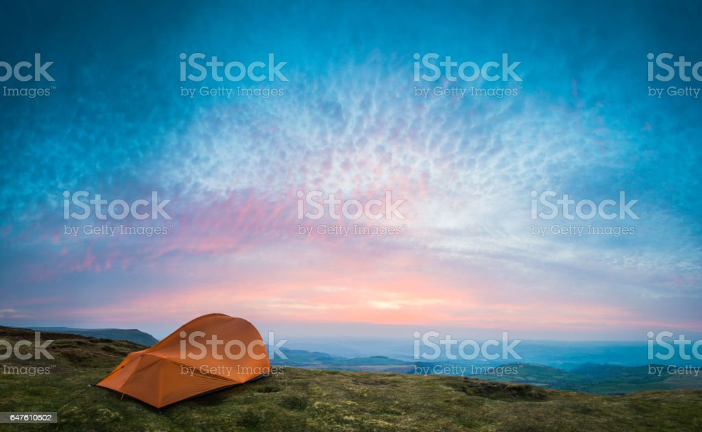 Camping tent on green mountain overlooking tranquil valley at sunset stock photo