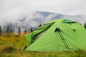 Camping tent outdoor in the nature forest with mist