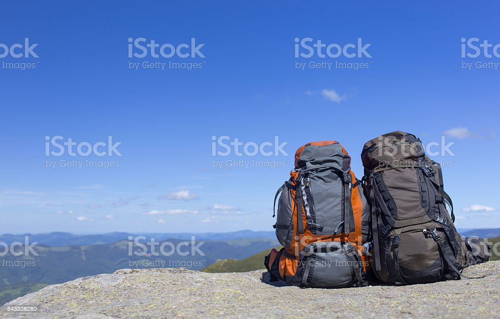 Camping with backpacks in the mountains against the blue sky. stock photo