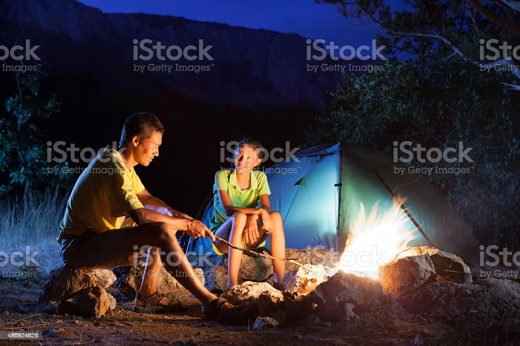 Camping with campfire at night stock photo