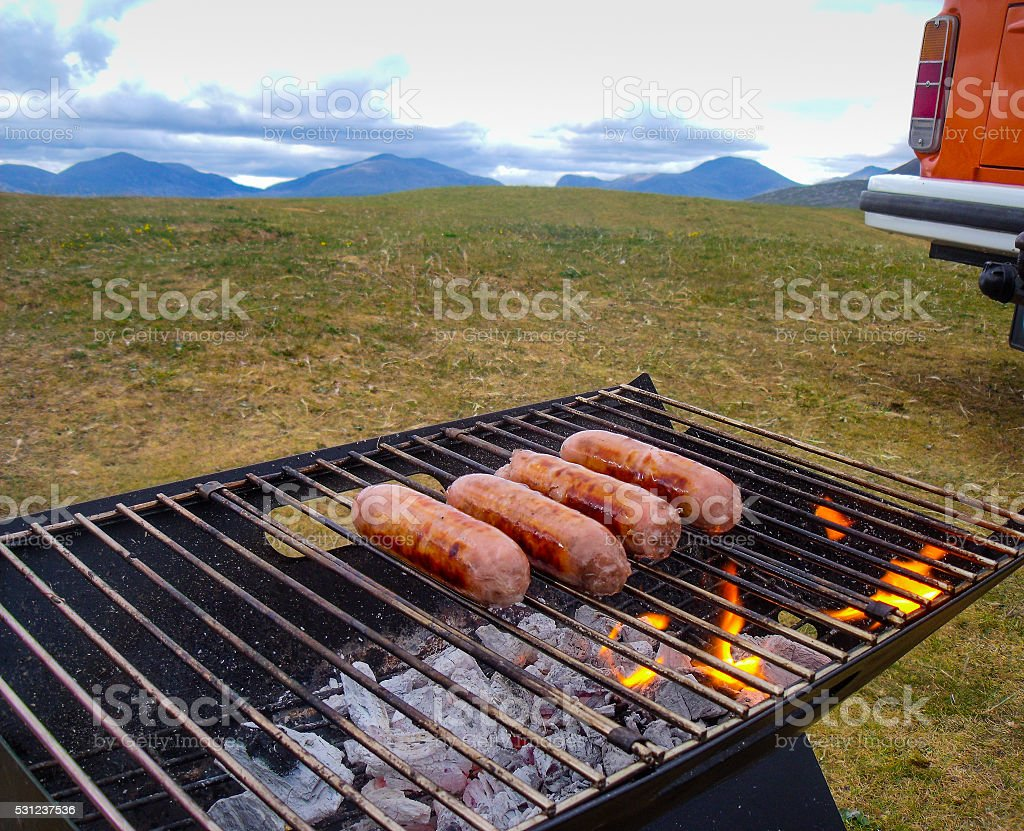 BBQ Camping with Sausages on Fiery Charcoal Grill stock photo