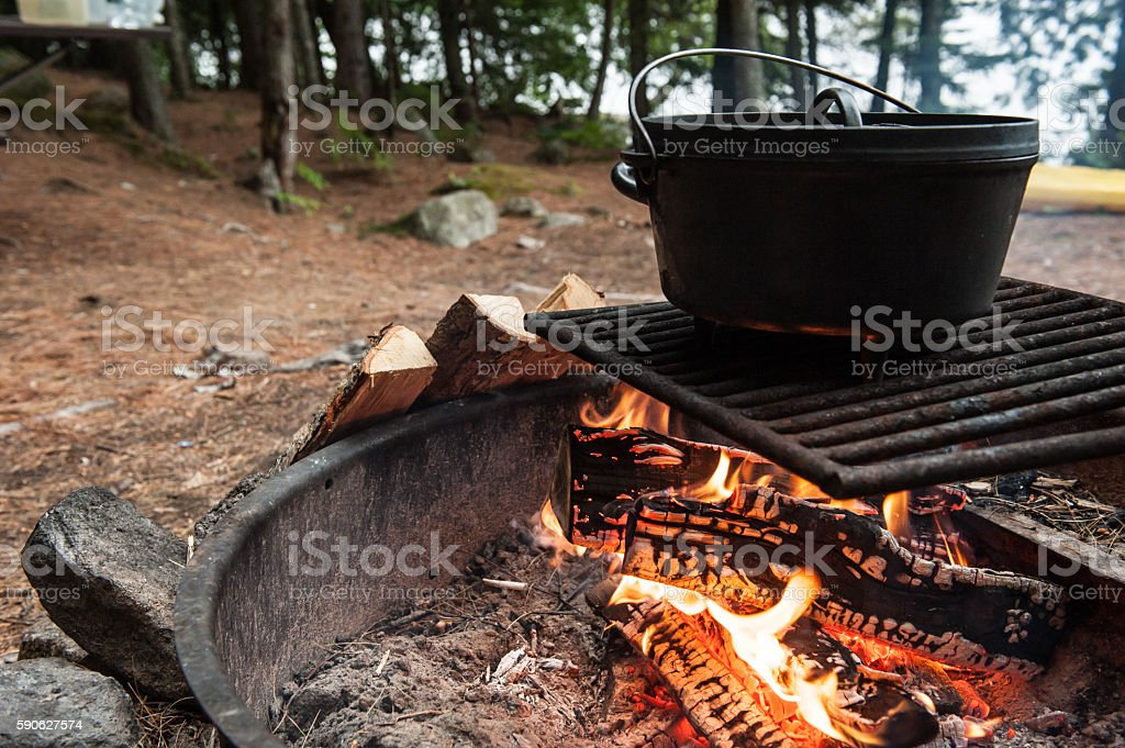 Campsite with a dutch oven cooking over a fire ring stock photo