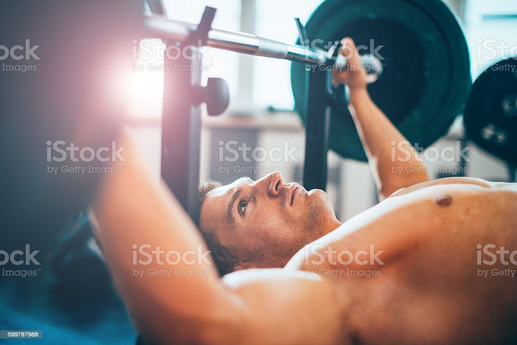 Portrait of topless body builder lifting weights on bench press in...