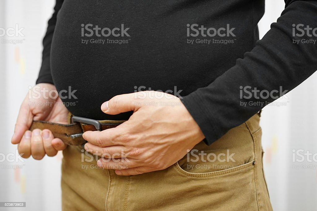 can not fasten his belt on  pants due tobig stomach stock photo