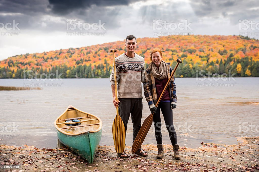 Canadian couple with a canoe in the park during fall stock photo