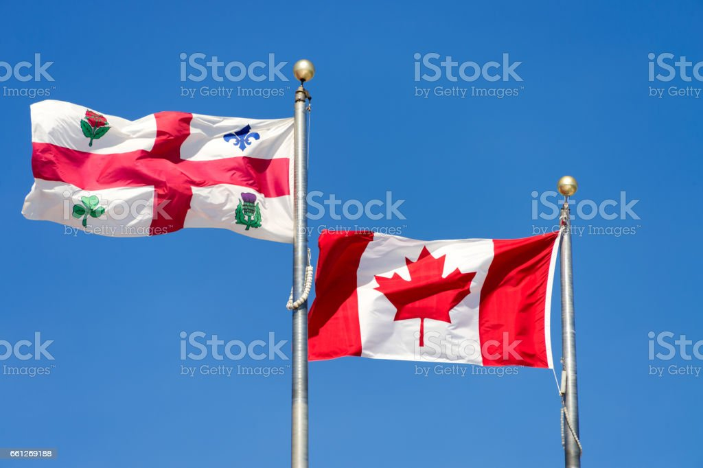 Canadian flag and Montreal city flag waving over blue sky stock photo