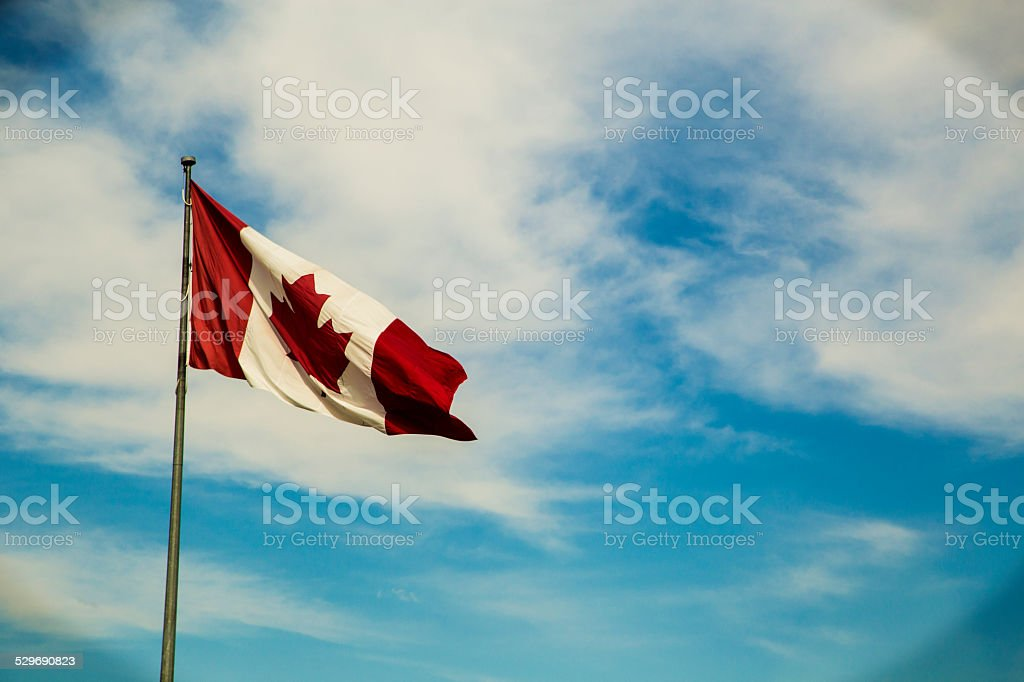 Canadian Flag blue sky background stock photo