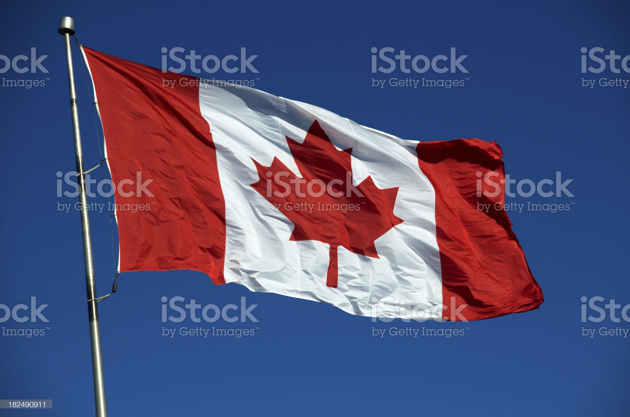 Canadian flag flying in the blue sky royalty-free stock photo