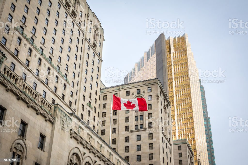 Canadian flag in front of business buildings & older skyscrapers stock photo