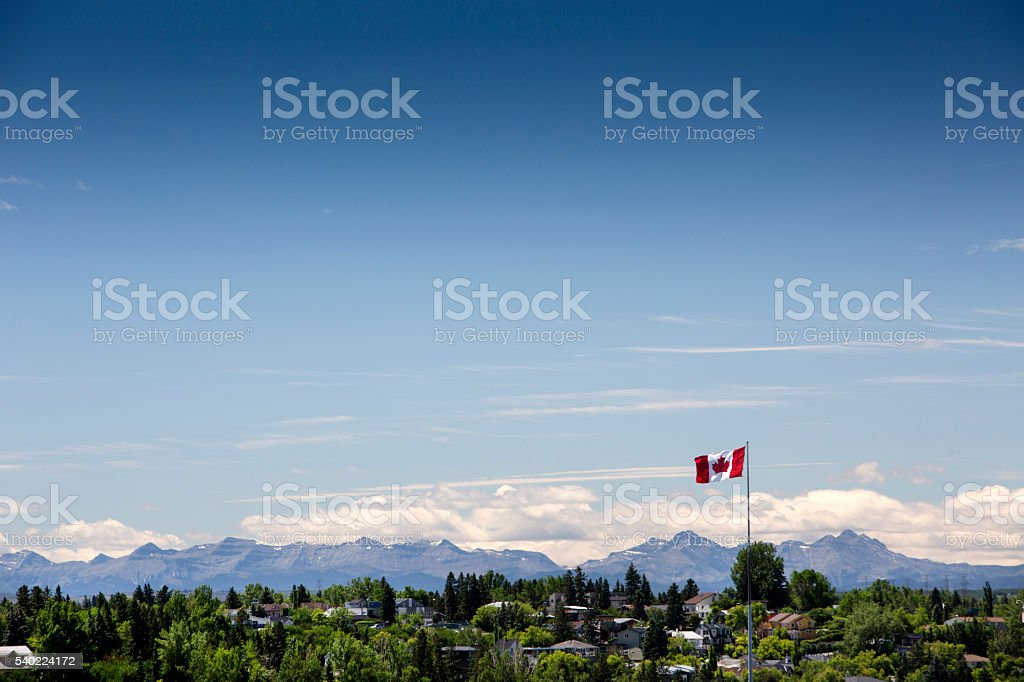 Canadian flag over the foothills and Canadian Rocky Mountains stock photo