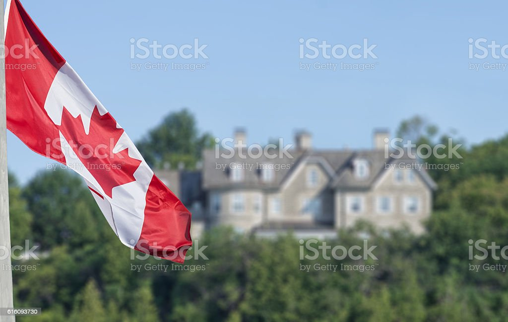 Canadian flag waving over 24 Sussex drive in blurred background stock photo