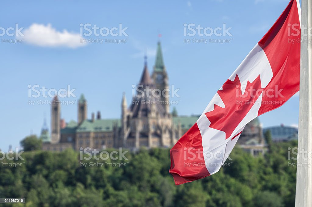 Canadian flag waving with Parliament Buildings hill and Library stock photo
