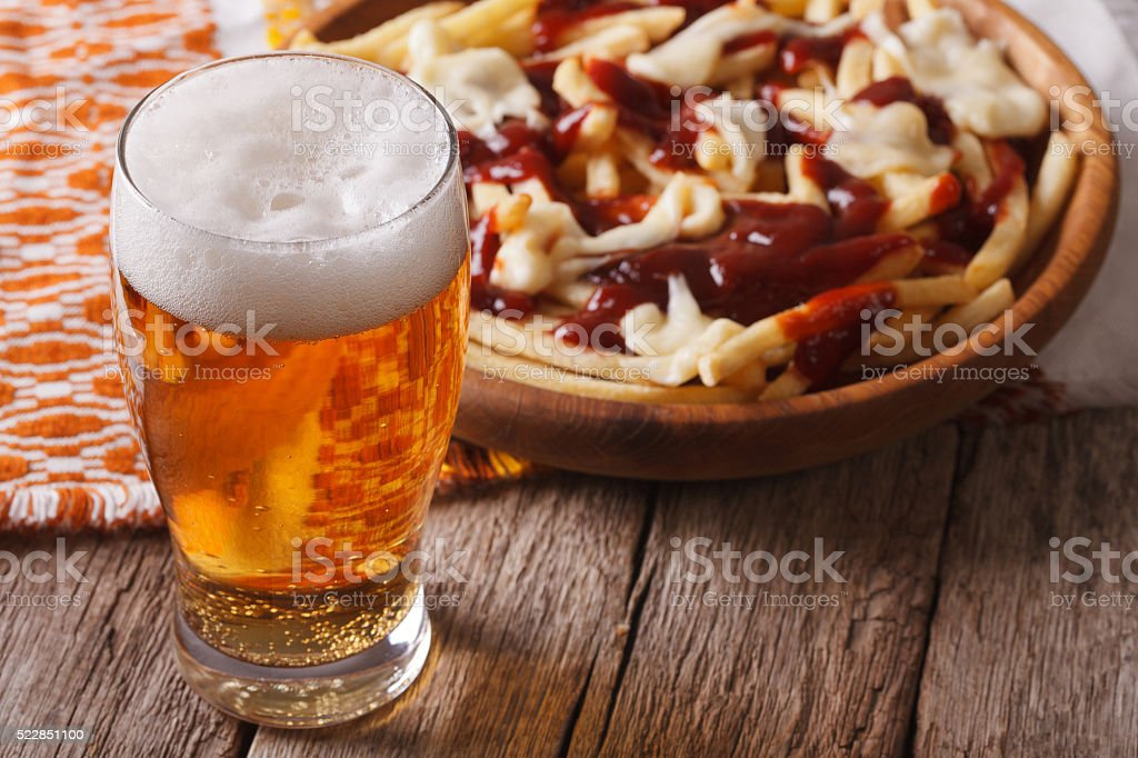 Canadian food: beer and fries with sauce close-up. horizontal stock photo
