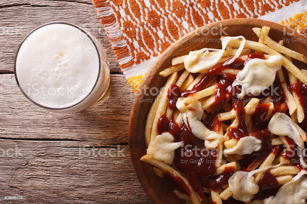 Canadian food: beer and fries with sauce close-up. horizontal to stock photo