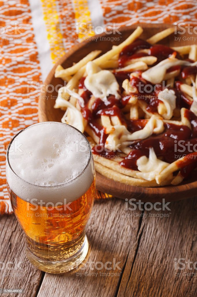 Canadian food: beer and fries with sauce close-up. Vertical stock photo