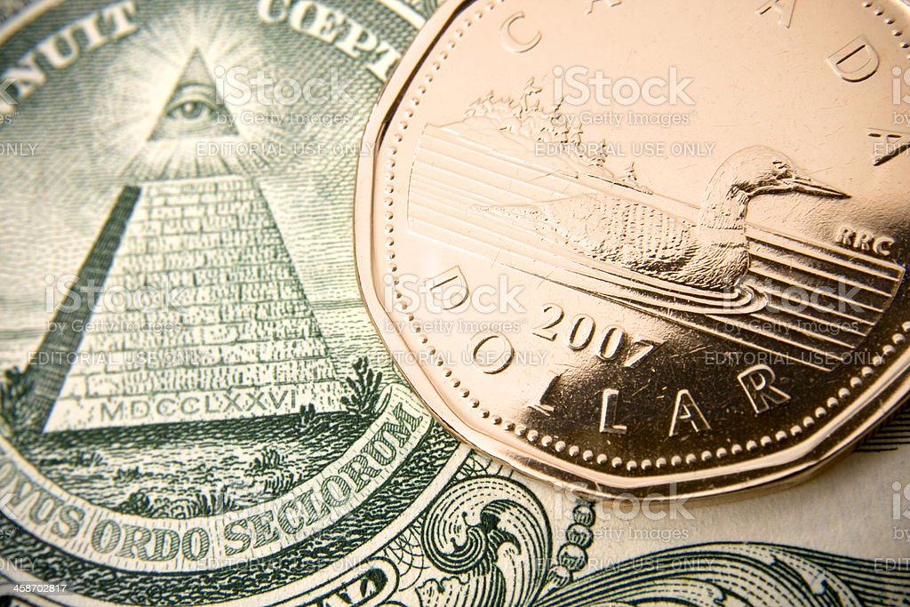 Canadian loonie on american currency stock photo