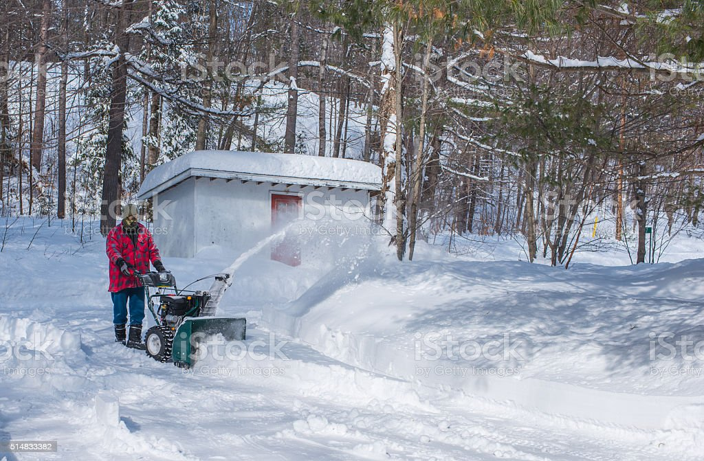 Canadian Man operates snow thrower on winter day in Canada. stock photo