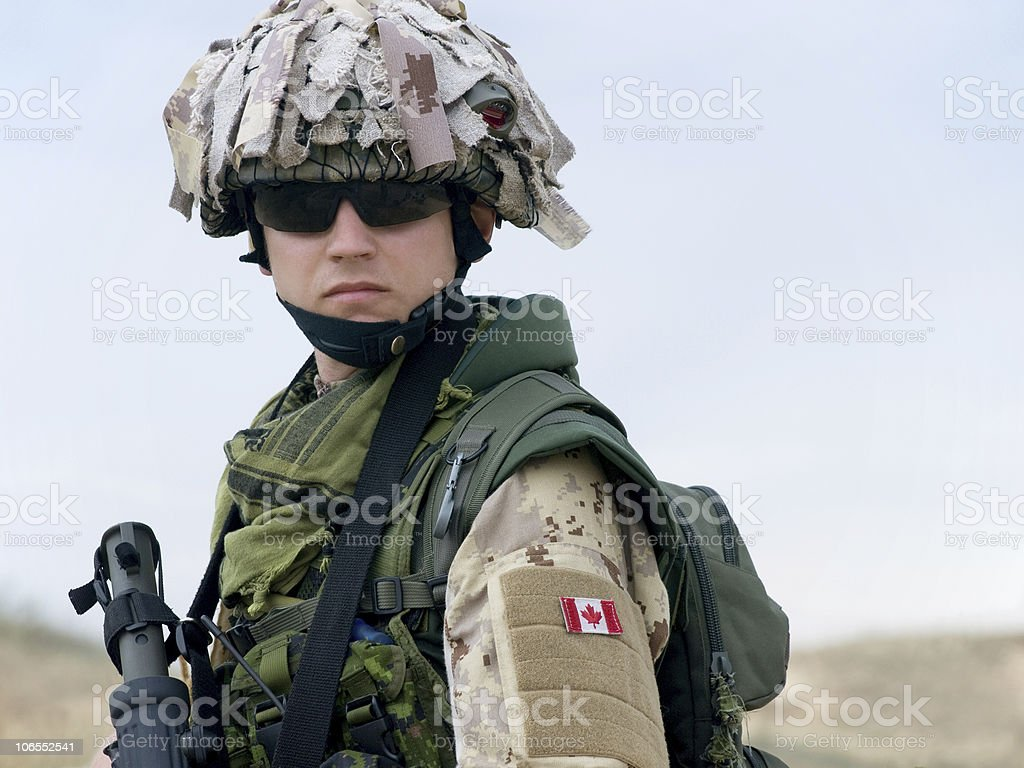 A Canadian soldier in a camouflaged uniform with a gun royalty-free stock photo