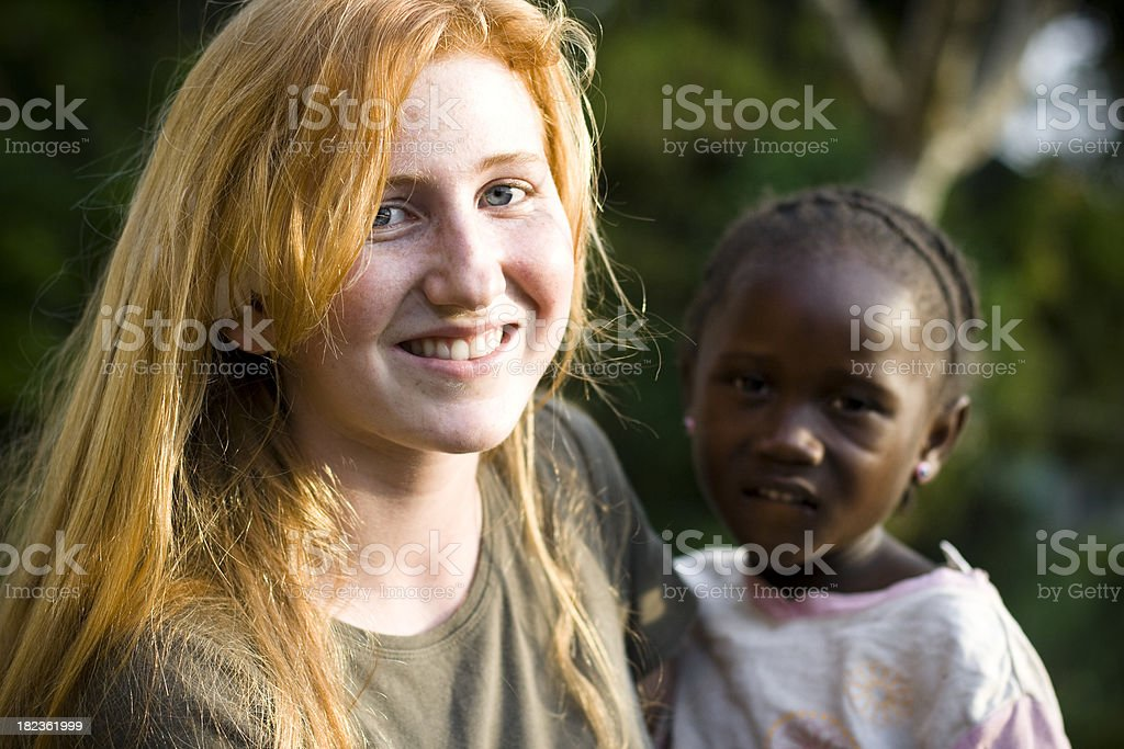 Canadian teen holding needy African child stock photo