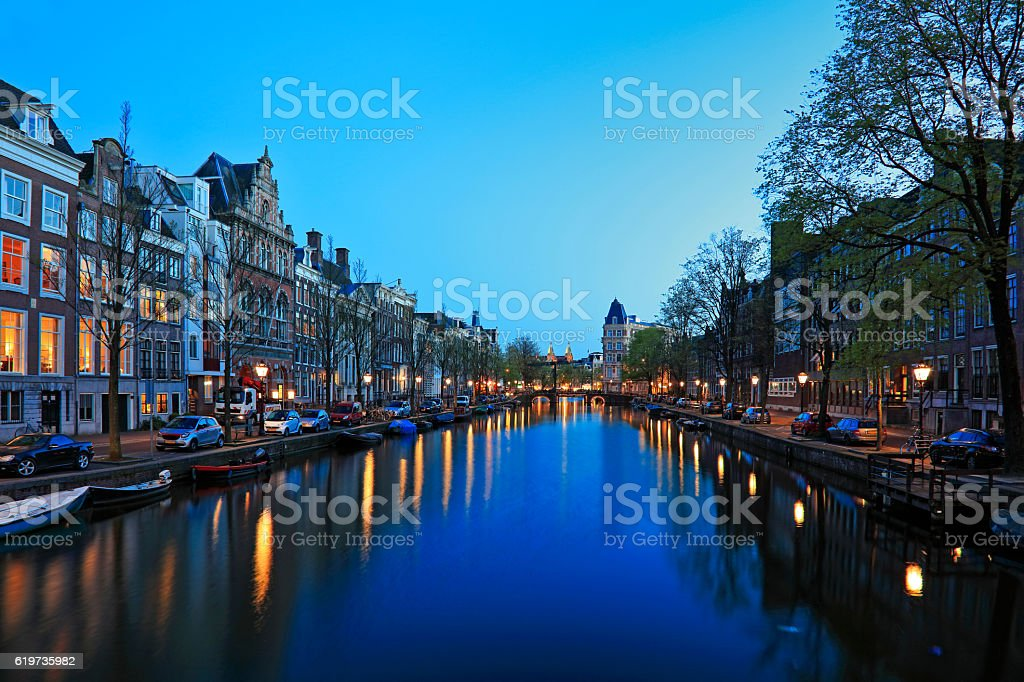 Canal Boat and Bridge at night, Amsterdam, Netherlands stock photo