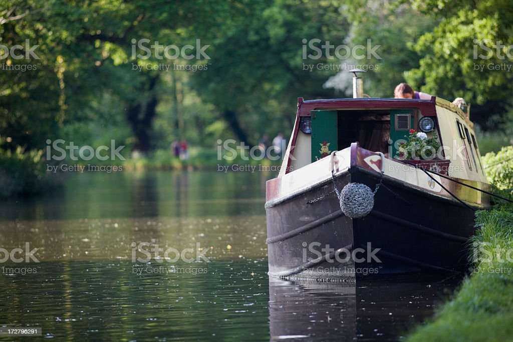 Canal boat moving down the river stock photo