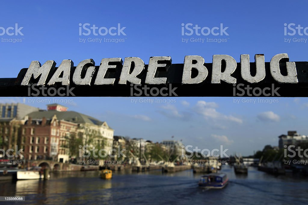canal boat passing Amsterdam's Magere Brug royalty-free stock photo