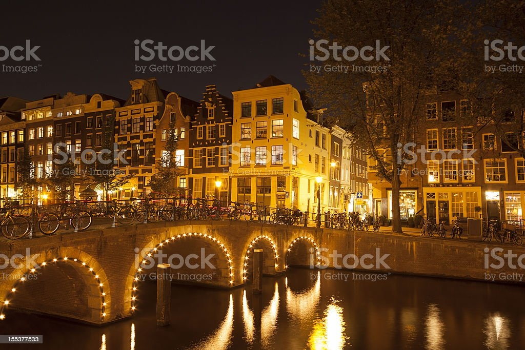 Canal bridge illuminated at night, Amsterdam, Netherlands stock photo