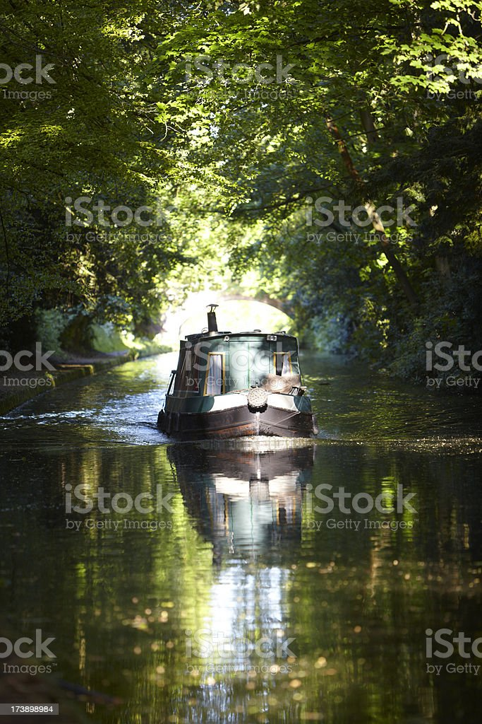 Canal Cruising on Narrowboat emerging from woods into sunlight stock photo