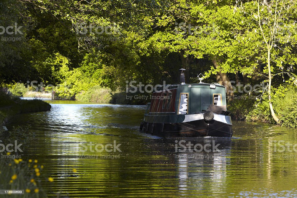 Canal narrowboat emerging into sunlight from woods stock photo