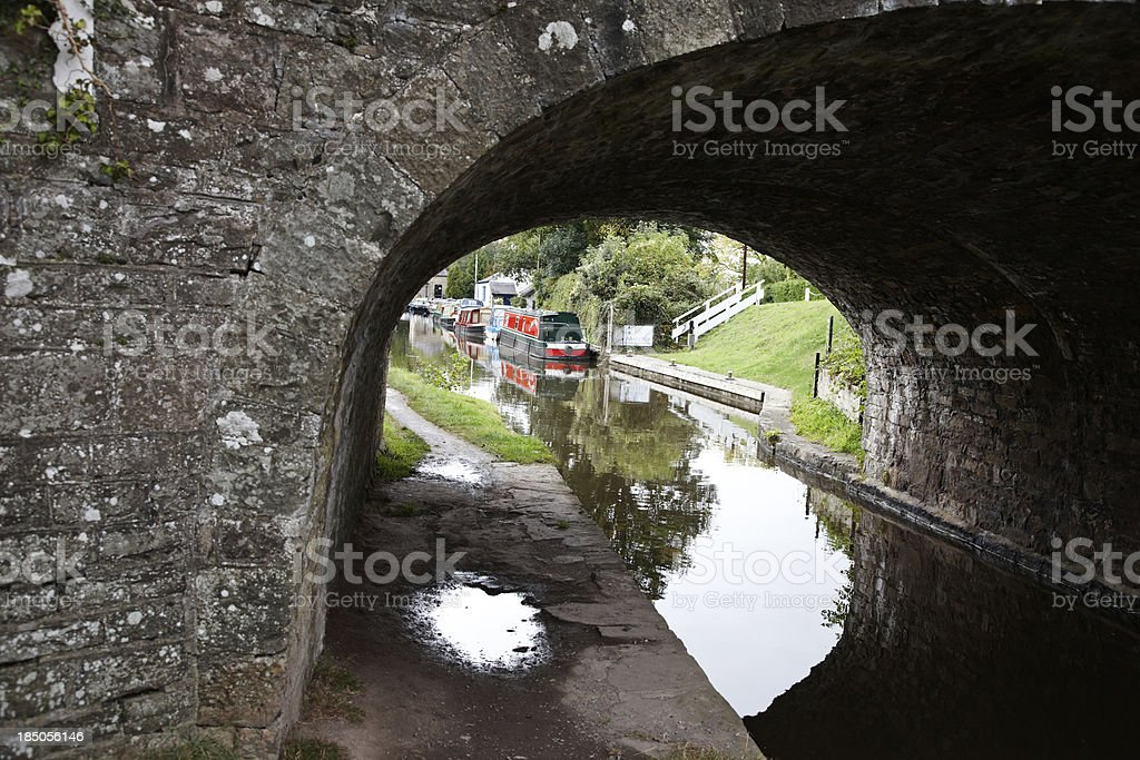 Canal side footpath and stone bridge stock photo