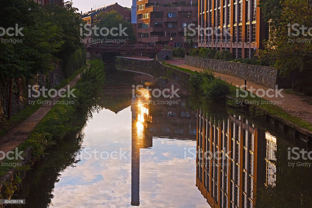 Canal waters with buildings and sun reflection, Washington DC, USA. stock photo