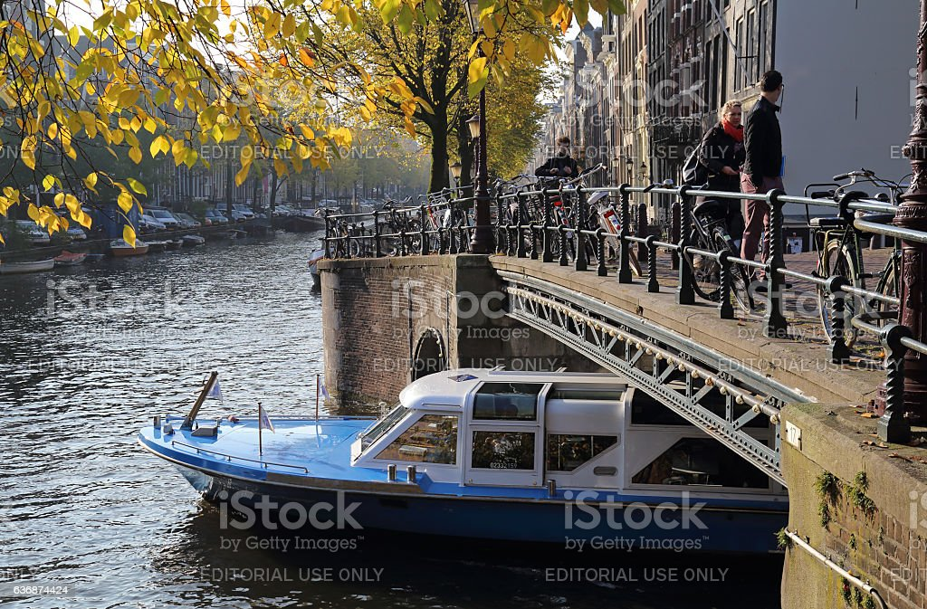 Canalboat in autumn in Amsterdam stock photo