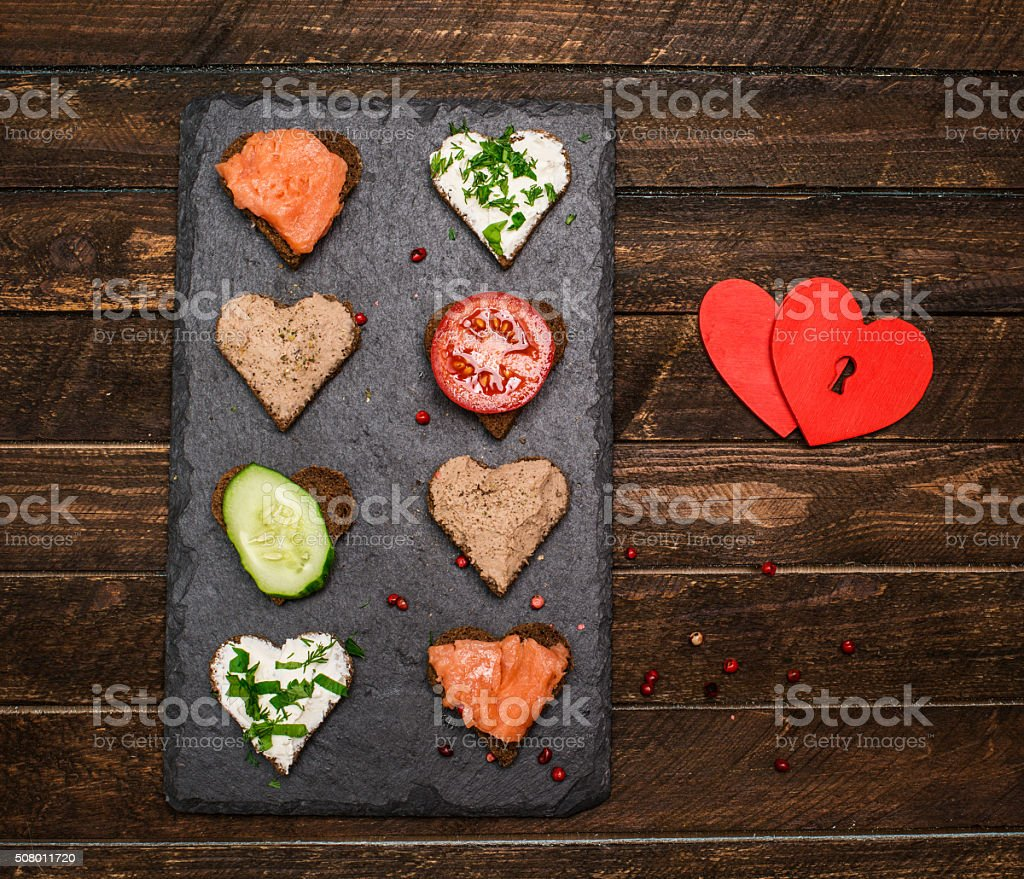 Canapes heart shape with different toppings on black slate board. stock photo