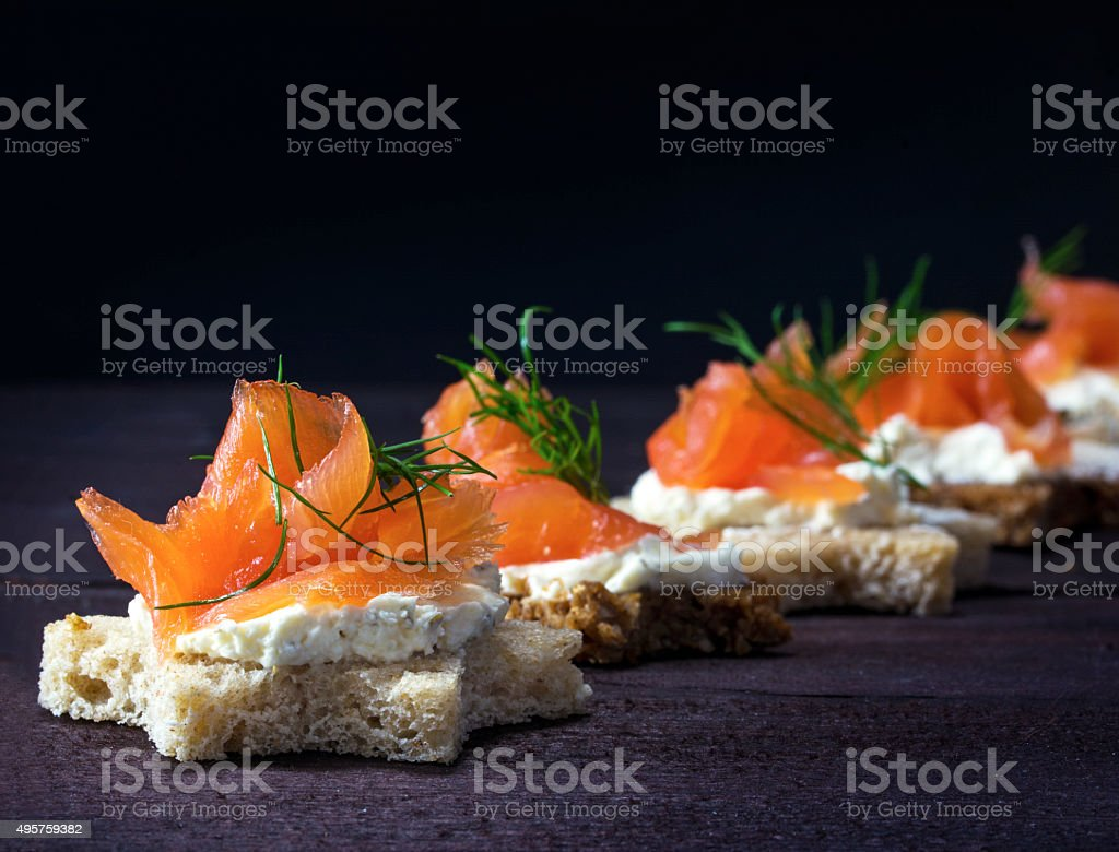 canapes in star shape with salmon on dark wood stock photo