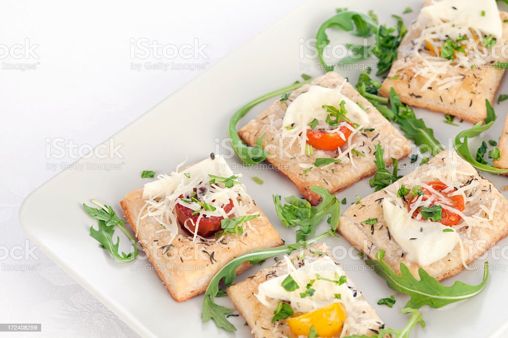 Canapes of puff pastry with tomato and mozzarella royalty-free stock photo