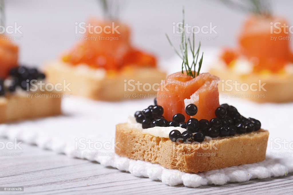 Canapes with black sturgeon caviar, salmon and dill. macro. stock photo