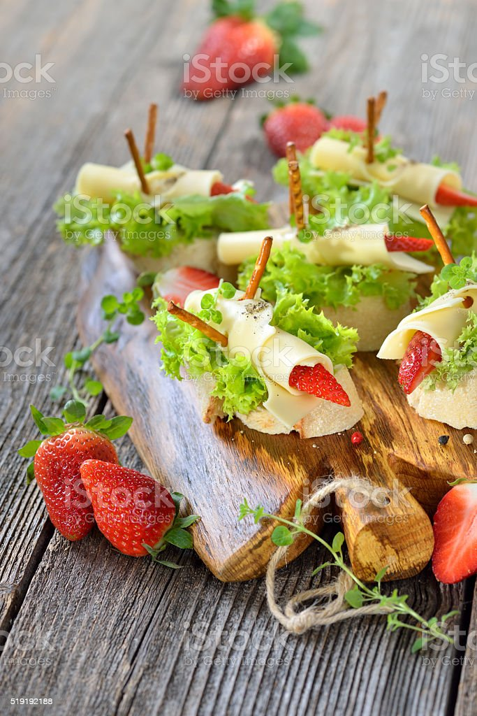 Canapes with cheese and strawberries stock photo