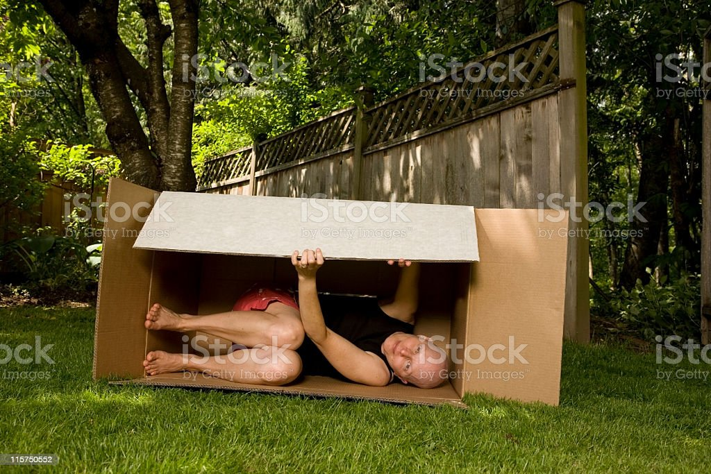 Cancer patient squeezes into a large box outside. royalty-free stock photo
