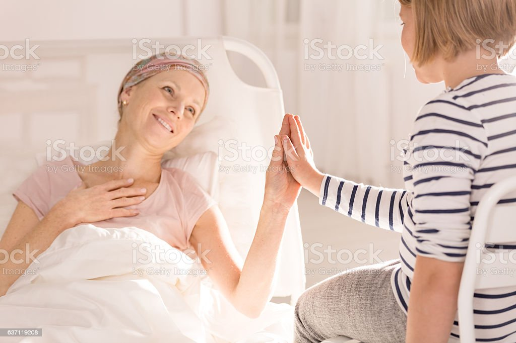 Cancer woman touching child's hand stock photo
