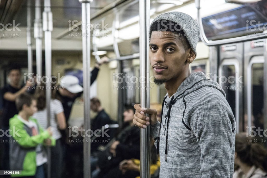 A candid, black man rides a crowded NYC subway train stock photo
