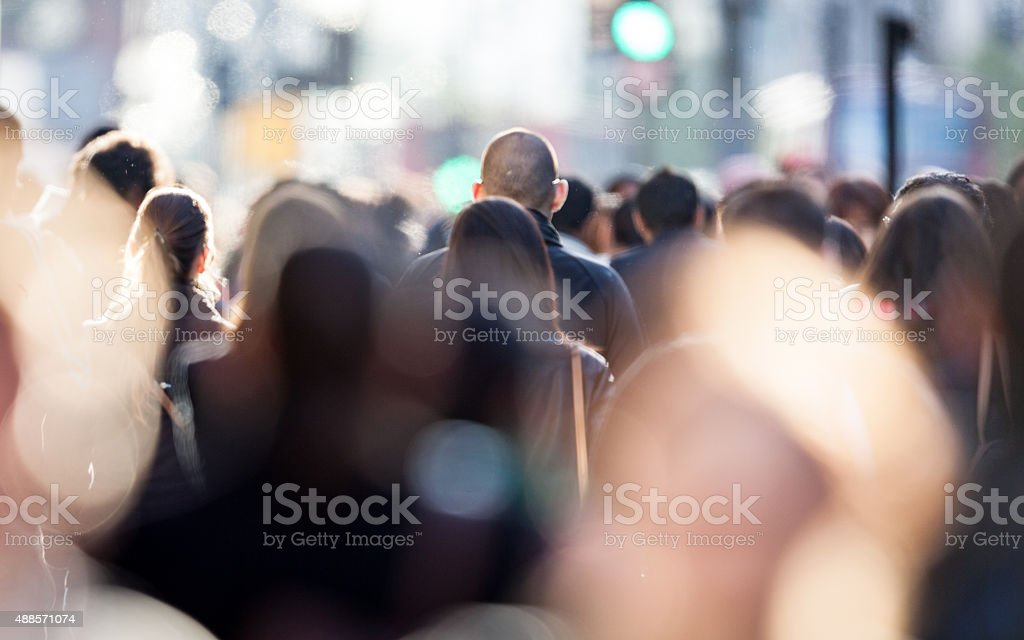 Heads of shoppers and commuters in a busy urban street scene.