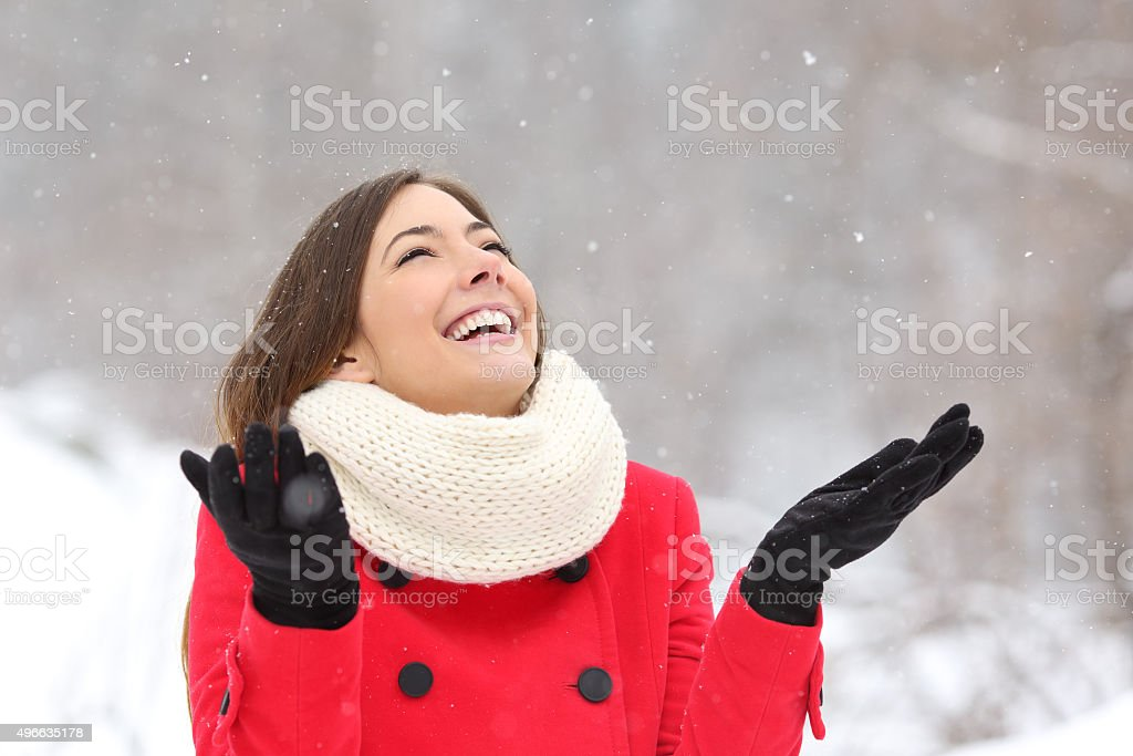 Candid happy girl enjoying snow in winter stock photo