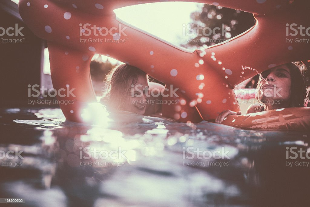 Candid image of girls in a pool on summer afternoon stock photo