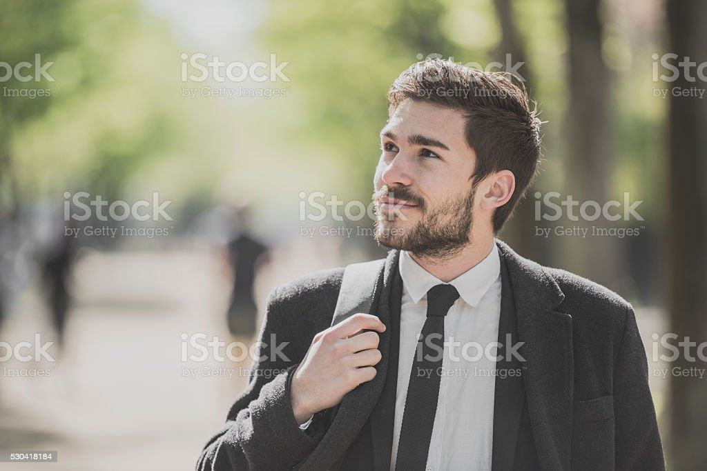 Candid outdoor portrait of young businessman walking to work stock photo