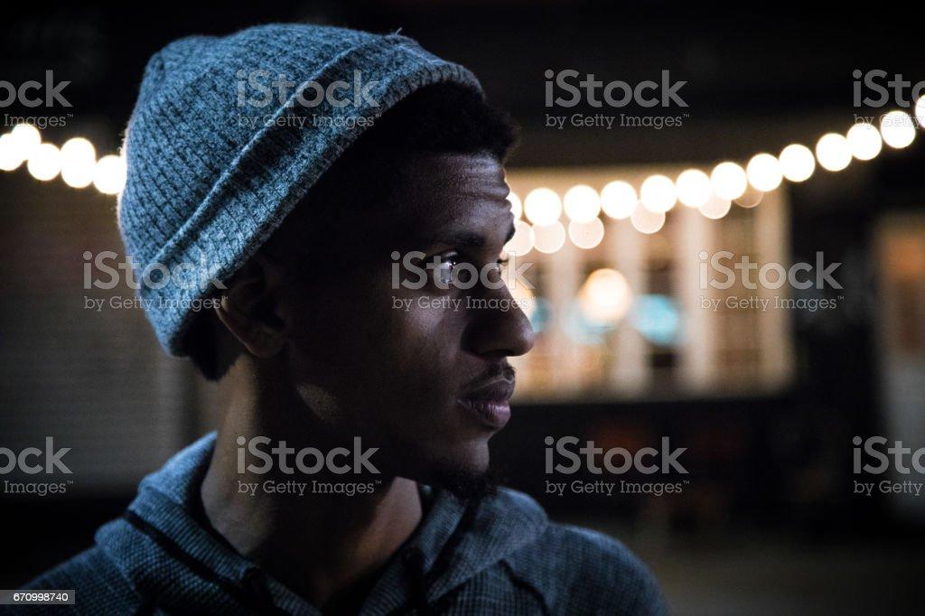 A candid portrait of a young, black man beneath Brooklyn Streetlights stock photo