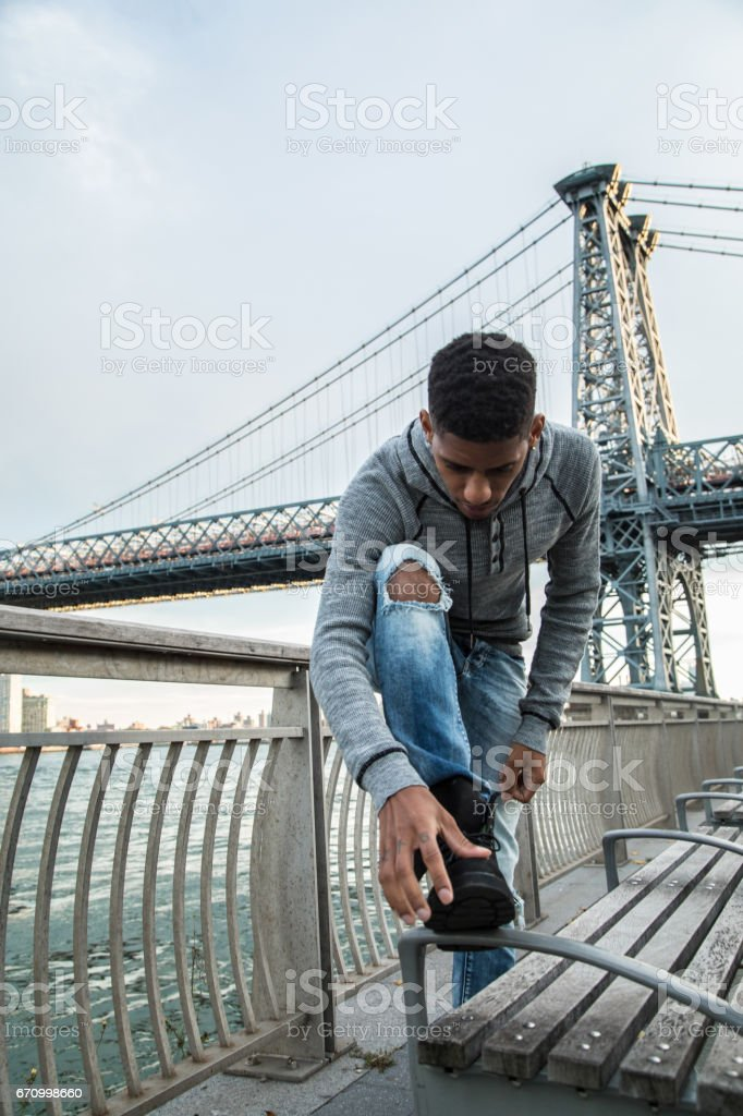 A candid portrait of a young, black man in front of NYC's Williamsburg Bridge at sunset stock photo
