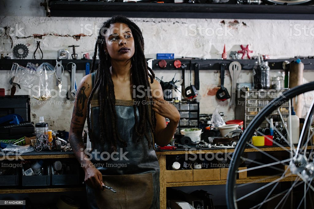 Candid portrait of afro-american bicycle mechanic standing in he stock photo