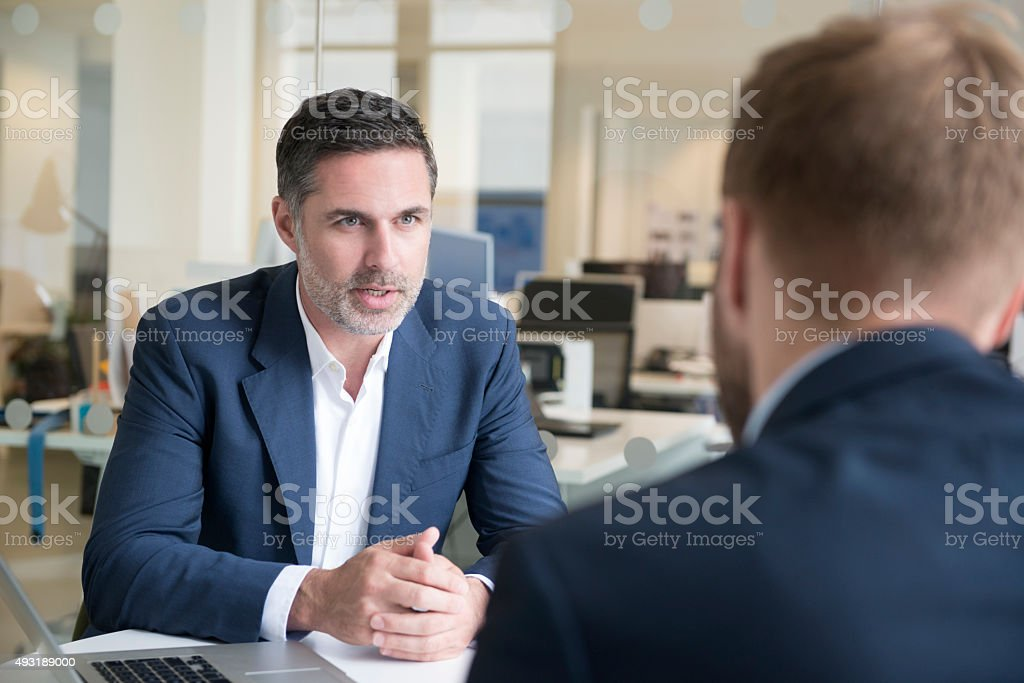 Candid portrait of businessman talking to colleague stock photo