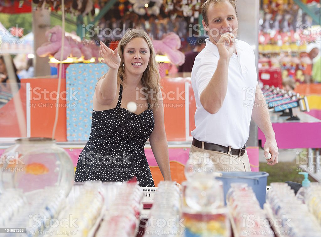 Candid Portrait of Couple at the Fair Playing Goldfish Game stock photo